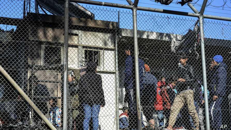 Migrants stand outside container houses in Moria refugee camp on the northeastern Aegean island of Lesbos, Greece, March 16, 2020.