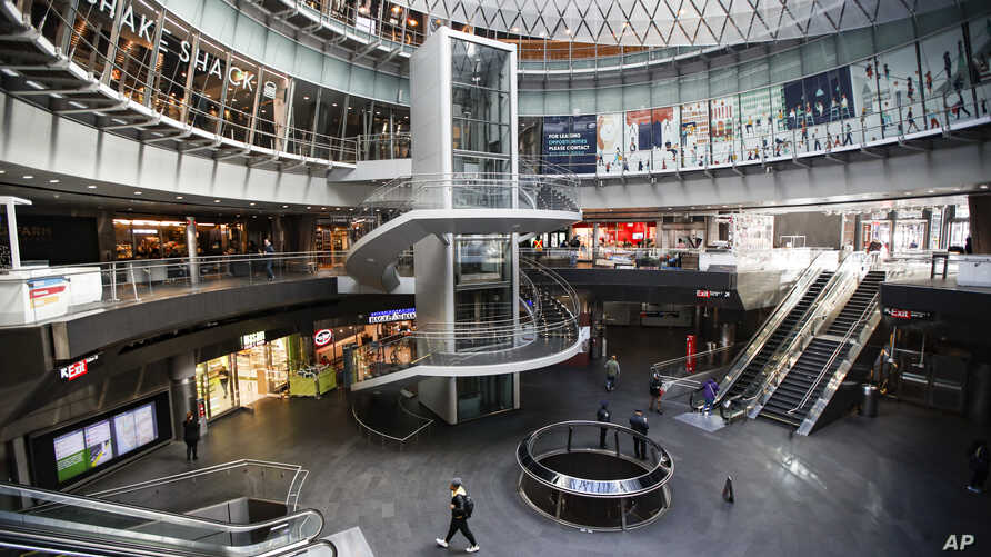 A pedestrian passes a nearly empty Fulton Center station as businesses are closed due to coronavirus concerns, Monday, March 16, 2020, in New York.