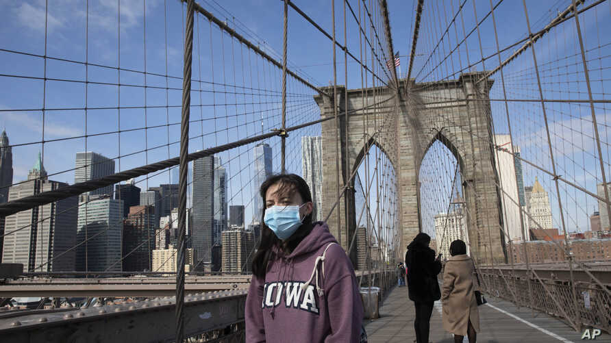 A woman wears a mask as she crosses the Brooklyn Bridge, Monday, March 16, 2020 in New York. The bridge's pedestrian path is…