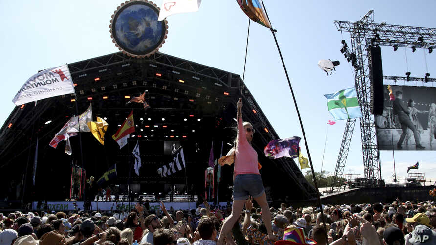 FILE - Revellers react to Kylie Minogue as she performs at the Glastonbury Festival, Somerset, England, June 30, 2019.