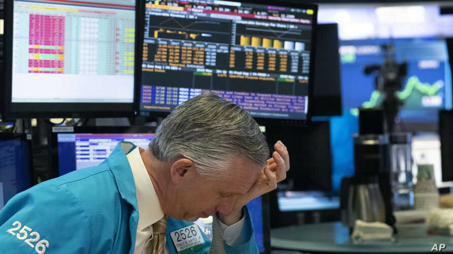 A trader holds his hand to his head after trading was halted at the New York Stock Exchange, Wednesday, March 18, 2020,  in New…