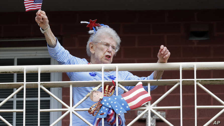 A resident of the Lambeth House, where a cluster of the coronavirus has formed, reacts from her balcony as opera singers Irini Hymel and Bryan Hymel sing to the quarantined residents in New Orleans, March 20, 2020.