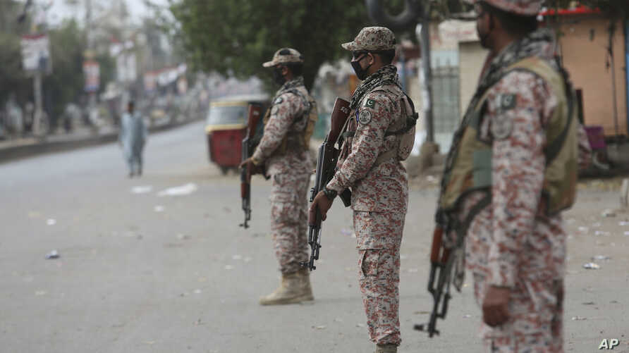 Security personnel stand guard after a government announced to lockdown the city concerns over the spread of the coronavirus,…