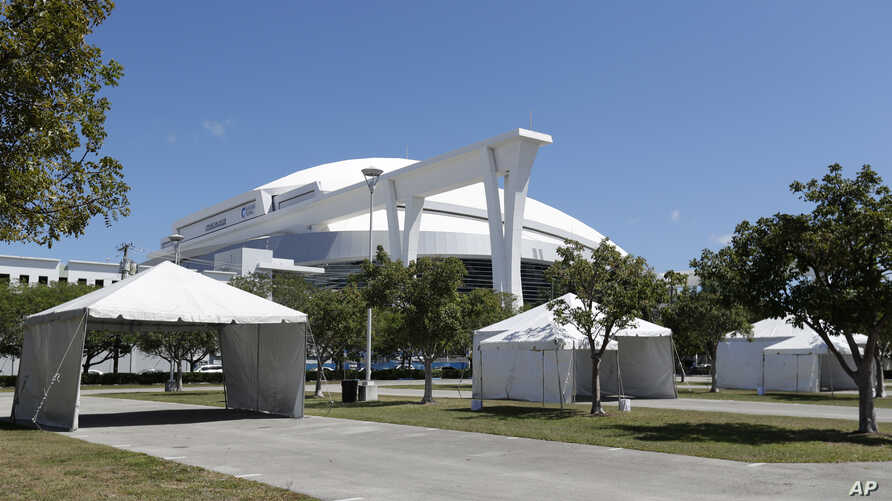 Tents are set up in a lot in front of the Marlins Park baseball stadium in preparation for a new drive through coronavirus testing site, March 23, 2020,in Miami.