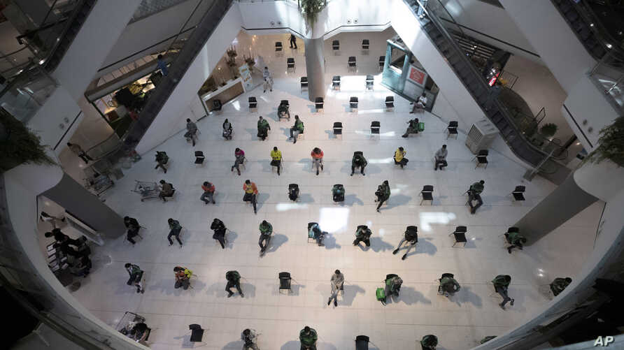 People practice social distancing as they sit on chairs spread apart in a waiting area for take-away food orders at a shopping mall in hopes of preventing the spread of the coronavirus in Bangkok, Thailand, March 24, 2020.