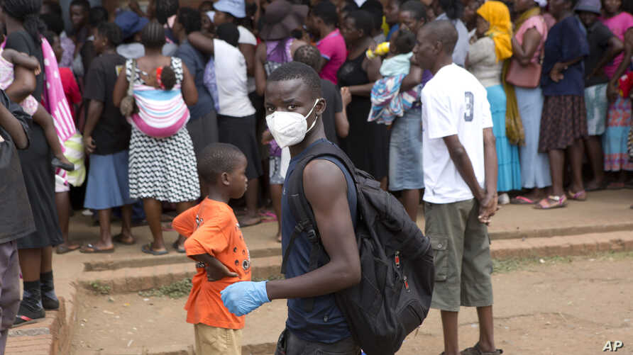 A man wearing a mask is seen near a food queue in Harare, Zimbabwe, March 25, 2020.