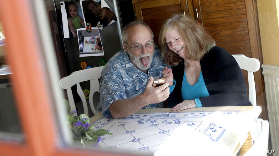 Seen through their kitchen window, Allan and Debbie Cameron contact their grandchildren via the internet Wednesday, March 25, 2020, in Chandler, Arizona. Debbie, 68, has asthma which makes her one of the people most at risk from the new coronavirus.