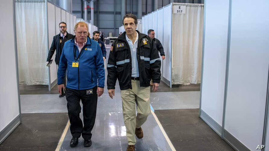 In this Friday, March 27, 2020, photo provided by Office of Governor Andrew M. Cuomo, Gov. Andrew Cuomo, right, walks the…