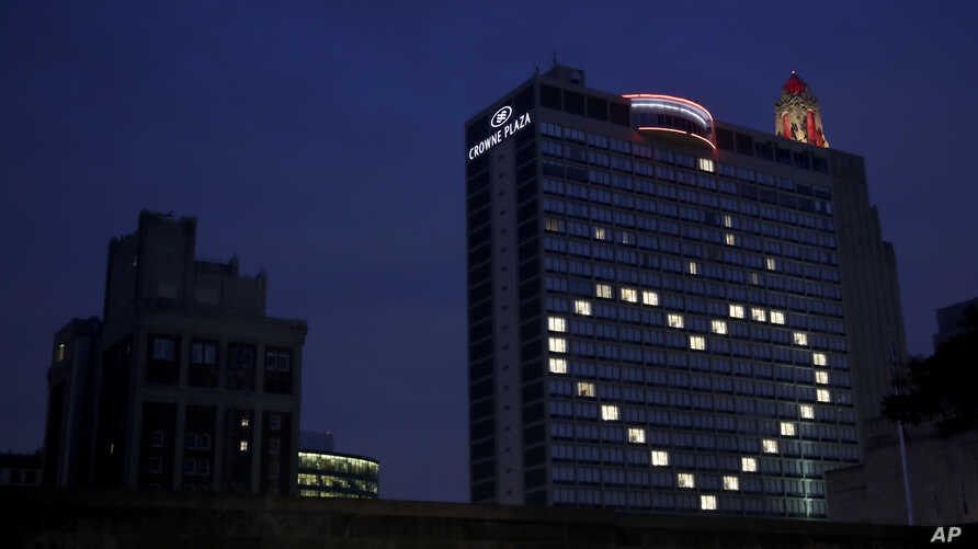 A downtown hotel leaves lights on in vacant room windows to form a heart Friday, March 27, 2020, in Kansas City, Mo.