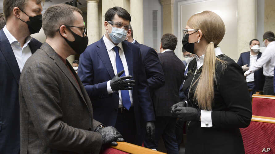 Ukraine's parliament speaker Dmytro Razumkov, center, and former Prime Minister Yulia Tymoshenko, right, wearing face masks to protect against coronavirus talk at an extraordinary parliamentary session in Kyiv, Ukraine, March 30, 2020.