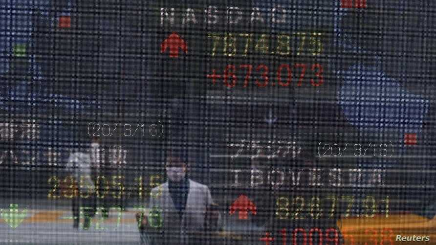 A woman wearing a protective face mask, following an outbreak of the coronavirus disease (COVID-19), is reflected in a screen displaying NASDAQ movements outside a brokerage in Tokyo, Japan March 16, 2020.