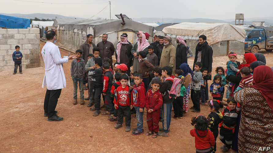 A doctor talks with refugees at a camp for displaced people in Atme, in Syria's northwestern Idlib province, near the border with Turkey, March 14, 2020.