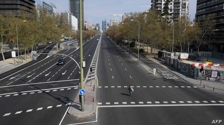 A woman crosses the usually busy La Castellana avenue in Madrid, Spain. France and Spain are the latest European nations to severely curtail people's movements to fight the coronavirus pandemic.