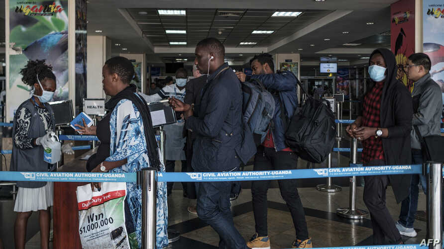 FILE - Passengers are asked to desinfect their hands upon arrival from international flights before being screened to detect signs of the coronavirus, at Entebbe Airport, in Entebbe, Uganda, March 3, 2020.