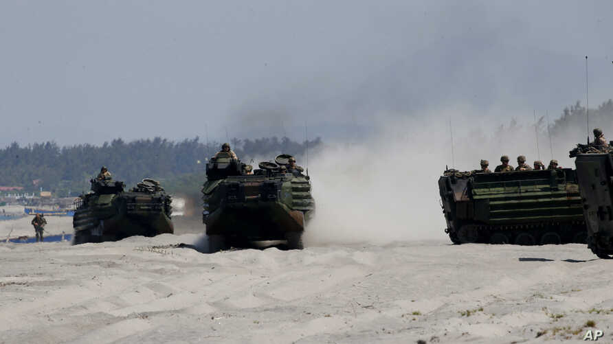 """FILE - Amphibious Assault Vehicles, carrying American and Philippine troops, are seen on a beach during """"Balikatan 2019"""" exercices, April 11, 2019, off San Antonio, Zambales province, northwest of Manila, Philippines."""