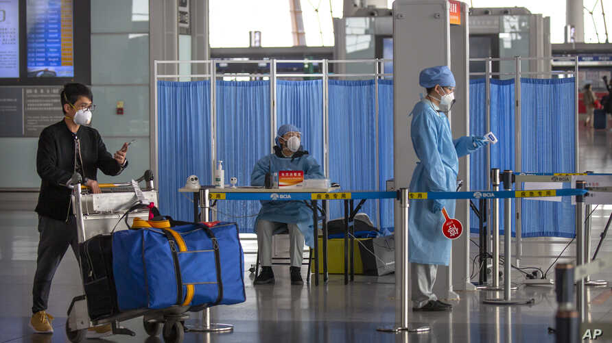 A man pushes his luggage past workers in protective suits as they wait to take the temperature of travelers at Beijing Capital International Airport in Beijing, March 6, 2020.