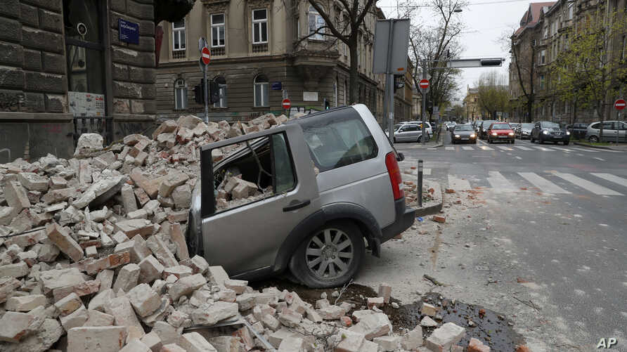 A car is crushed by falling debris after an earthquake in Zagreb, Croatia, March 22, 2020.