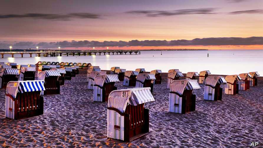 FILE - Beach chairs are lined up before sunrise in Timmendorfer Strand at the Baltic Sea, northern Germany, Aug. 21, 2018.