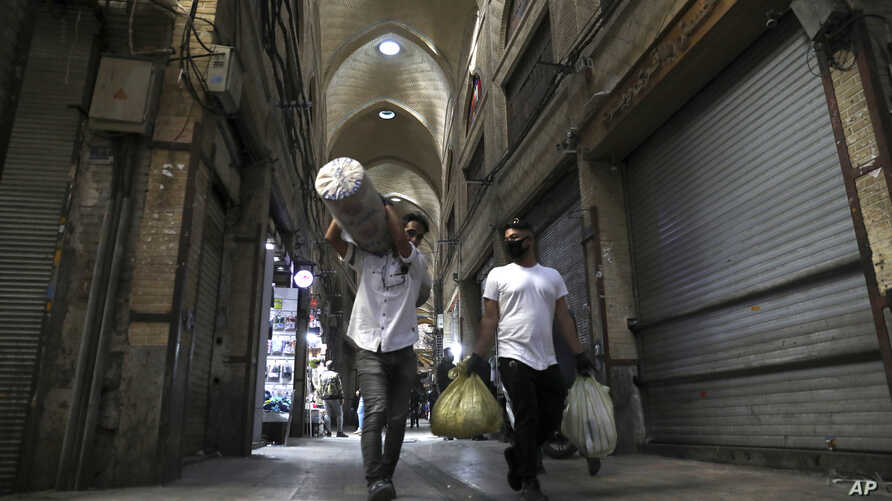 Men carry their goods through mostly closed Tehran's Grand Bazaar, Iran, March 17, 2020.