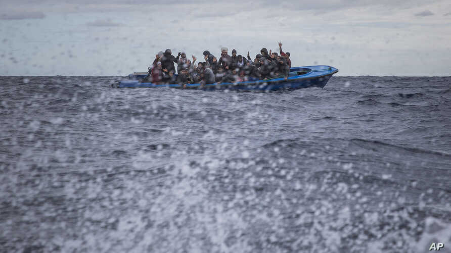 FILE - Men from Morocco and Bangladesh react on an overcrowded wooden boat, as aid workers of the Spanish NGO Open Arms approach them in the Mediterranean Sea, international waters, off the Libyan coast, Jan. 10, 2020.