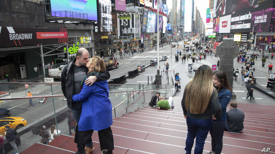 A couple kisses as they pose for a photo at the top of the TKTS stairs, March 10, 2020, in New York's Times Square.