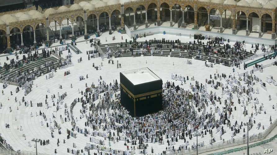 A relatively few number of Muslims pray around the Kaaba, the cubic building at the Grand Mosque, in the Muslim holy city of Mecca, Saudi Arabia, March 4, 2020.