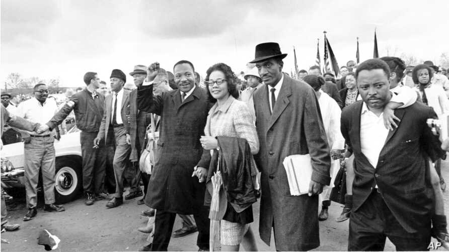 FILE - Dr. Martin Luther King Jr., and his wife, Coretta Scott King, front row-left, lead the final lap to the state capitol in Montgomery, Alabama, March 25, 1965, as thousands of marchers walk to demand voting rights for African Americans.