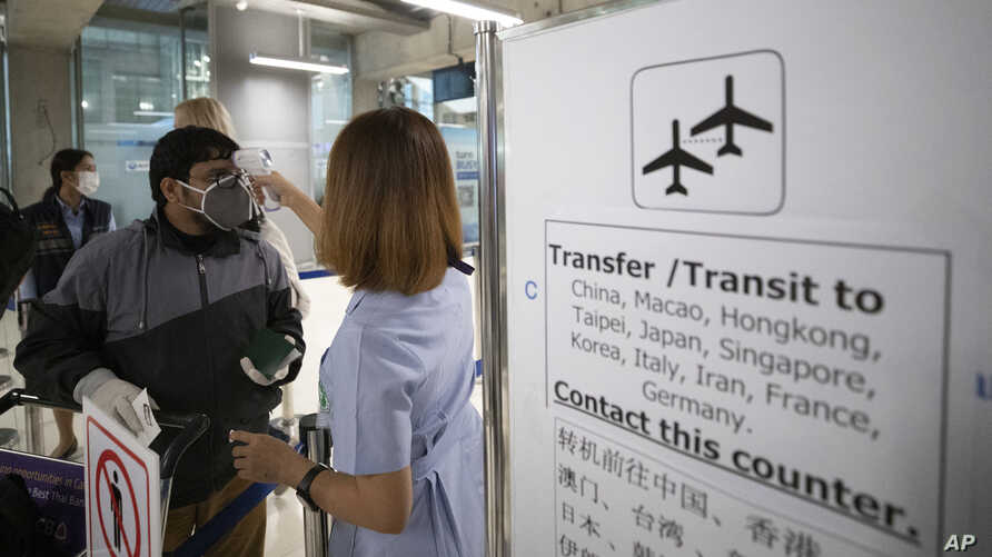 A health worker checks tourists' temperatures as they arrive at Suvarnabhumi Airport, in Bangkok, Thailand, March 4, 2020.