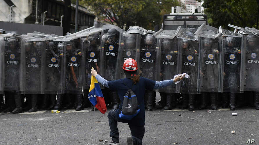 A man kneels in front of police blocking a march called by opposition political leader Juan Guaido in Caracas, Venezuela.