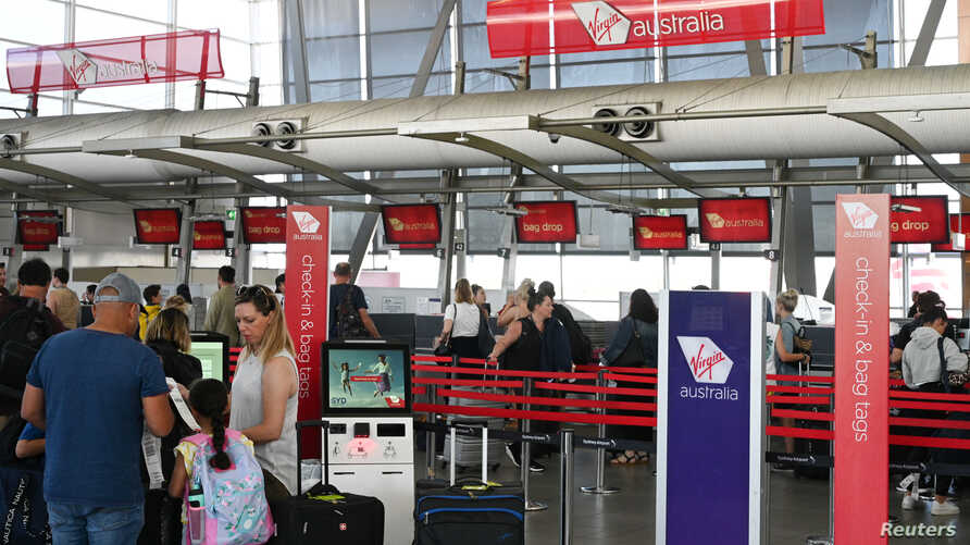 Travelers wait in line at a Virgin Australia Airlines counter at Kingsford Smith International Airport, amid the coronavirus outbreak, in Sydney, Australia, March 18, 2020.