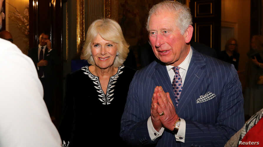 """FILE - Britain's Prince Charles, with Camilla, Duchess of Cornwall, at his side, folds his hands in a """"namaste"""" greeting, during a reception at Marlborough House, in London, Britain, March 9, 2020."""