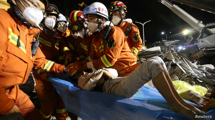 Rescue workers wearing protective masks extract a boy from the rubble of a collapsed hotel which was being used as a quarantine facility for coronavirus patients, in the southeastern port city of Quanzhou, China, March 9, 2020.