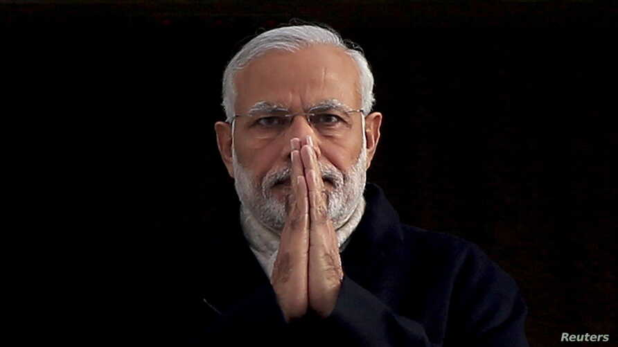 """FILE - India's Prime Minister Narendra Modi holds up his hands in a """"namaste,"""" a traditional Indian greeting, as he arrives for an official visit to Britain, in London, Nov. 12, 2015."""