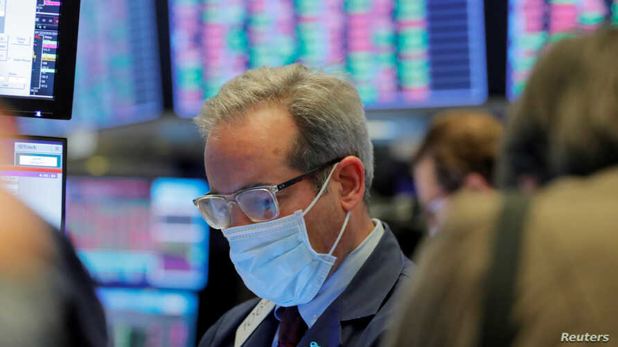 FILE - A trader wears a protective mask as he works on the floor of the New York Stock Exchange (NYSE), in New York City, March 20, 2020.