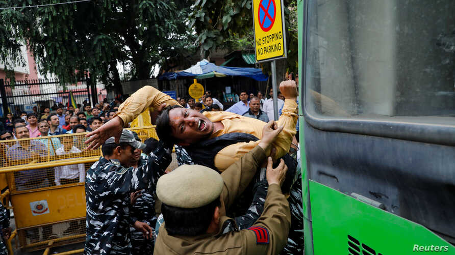 Police detains an activist of the youth wing of India's main opposition Congress party during a protest demanding the resignation of Home Minister Amit Shah following last week's clashes in New Delhi.
