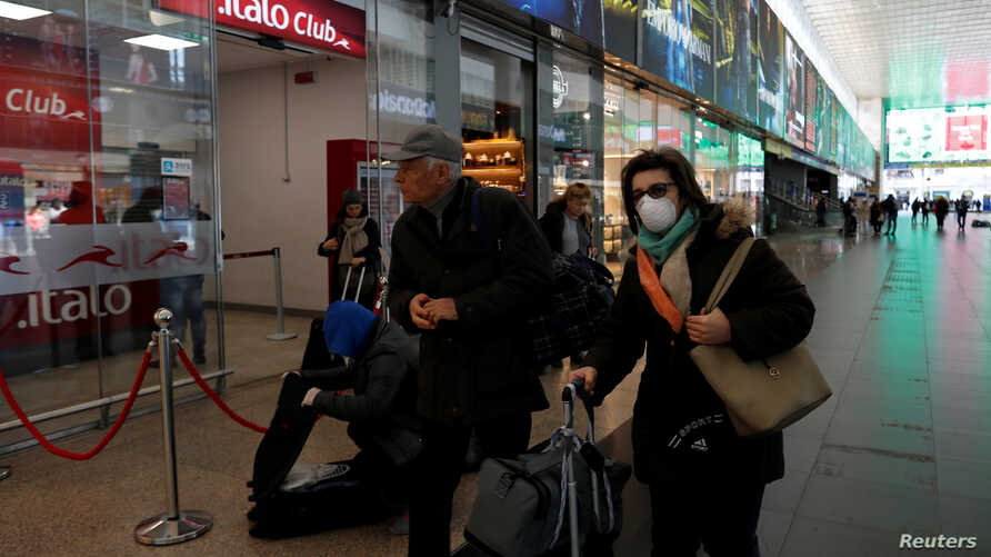 A woman wears a protective face mask at Roma Termini railway station, after the Italian government imposed a virtual lockdown on the north of the country, in Rome, March 8, 2020.