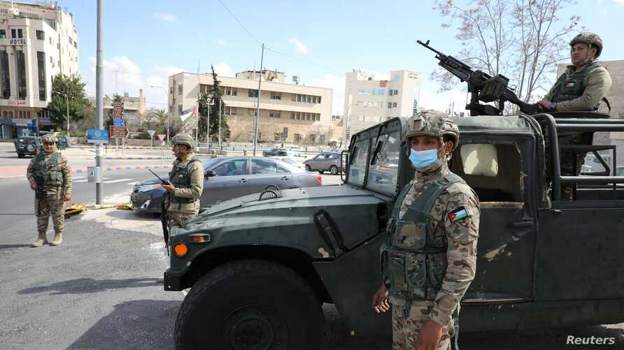 Jordanian army members stand guard outside a hotel that was transformed into a quarantine station amid concerns over the coronavirus (COVID-19) in Amman, March 17, 2020.