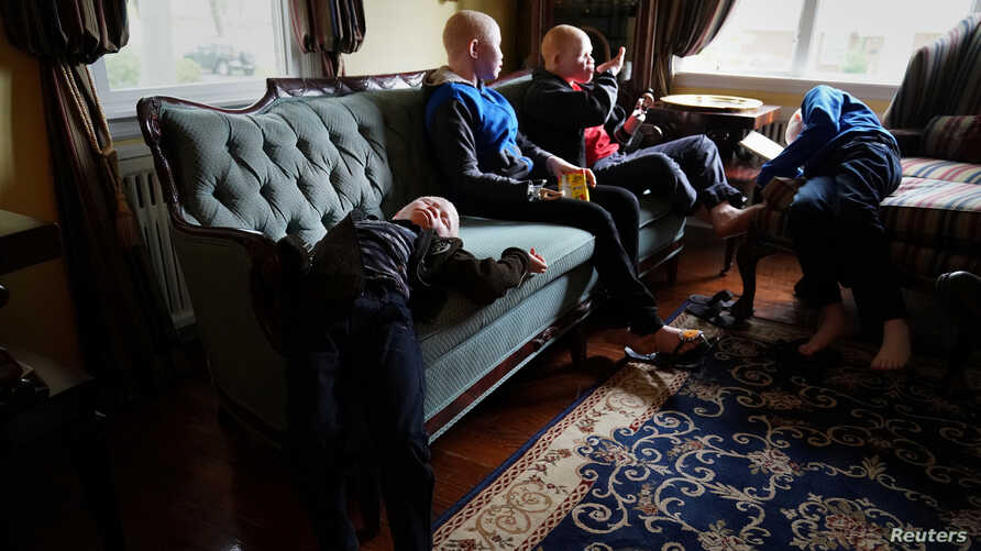 FILE - Baraka Lusambo, 7, Pendo Noni 16, Emmanuel Rutema, 15, and Mwigulu Magesaa 14, Tanzanians with albinism who had body parts chopped off in witchcraft-driven attacks, relax at a home in the Staten Island borough of New York City, June 4, 2017.