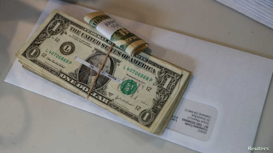 Tips, money collected from a customer donation fund and a last paycheck for employees laid off from Farley's East cafe, that closed due to the coronavirus outbreak, sits on a counter at the cafe in Oakland, California, March 18, 2020.