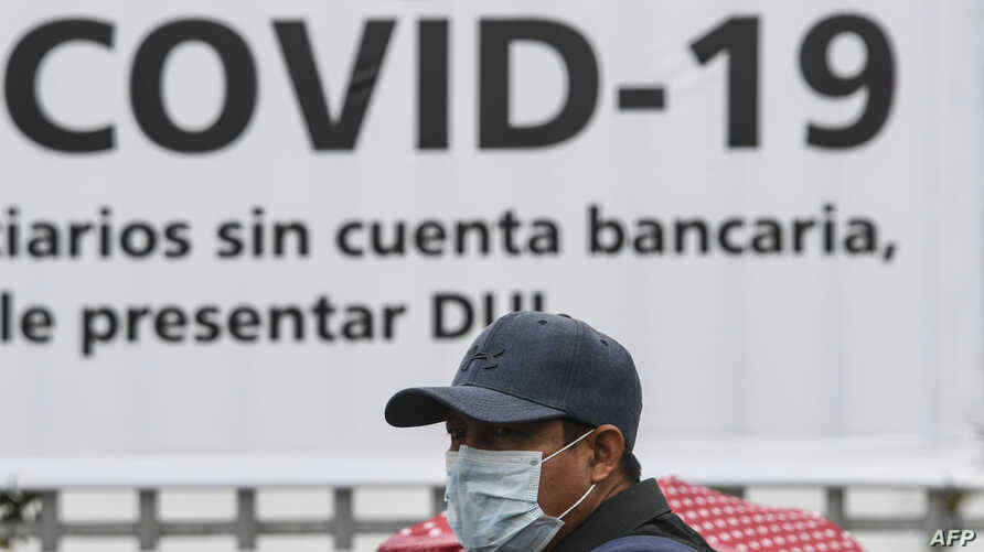A man wears a face mask against the spread of the new coronavirus (COVID-19) as he waits to enter a bank to receive a $300 USD…