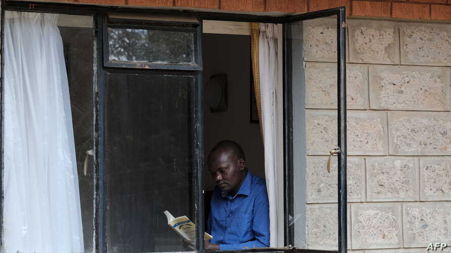 A man reads a book to pass the time at a Government designated quarantine facility in Nairobi on April 04, 2020. - Hundreds of…