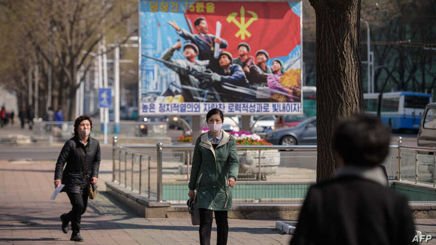 People wearing face masks walk before a propaganda poster displayed on a street in Pyongyang on April 9, 2020. (Photo by KIM…