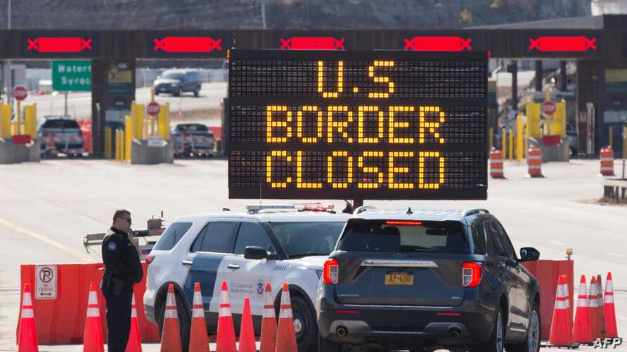 (FILES) In this file photo US Customs officers speaks with people in a car beside a sign saying that the US border is closed at…