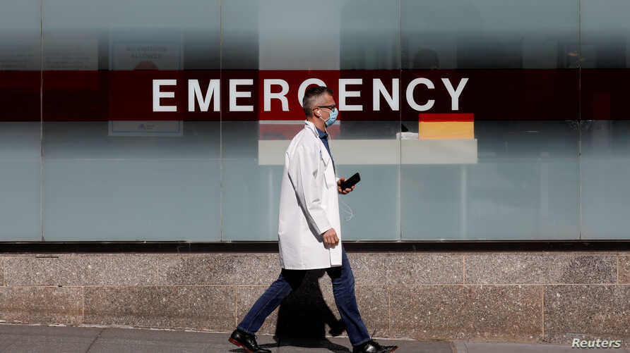 FILE PHOTO: A doctor wears a protective mask as he walks outside Mount Sinai Hospital in Manhattan during the outbreak of the…
