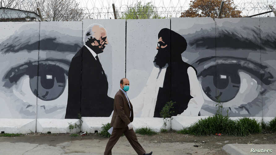 An Afghan man wearing a protective face mask walks past a wall painted with photo of Zalmay Khalilzad, U.S. envoy for peace in…