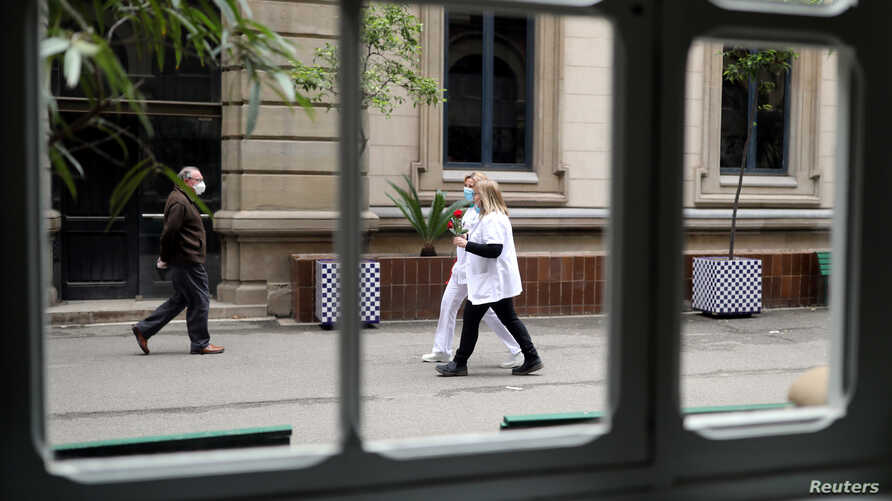People are seen holding roses outside the Hospital Clinic on Saint George's Day (Sant Jordi)