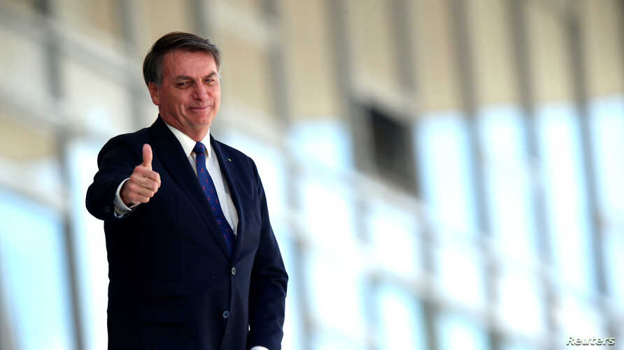 Brazil's President Jair Bolsonaro gestures as he stands at the ramp of the Planalto Palace, amid the coronavirus disease (COVID…