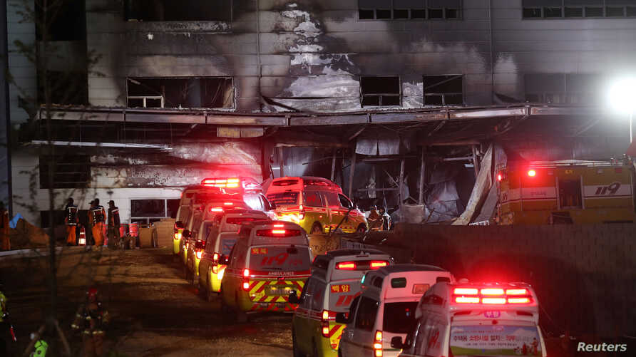 Ambulances are parked outside a damaged warehouse which is currently under construction, after it caught fire, in Icheon, South…