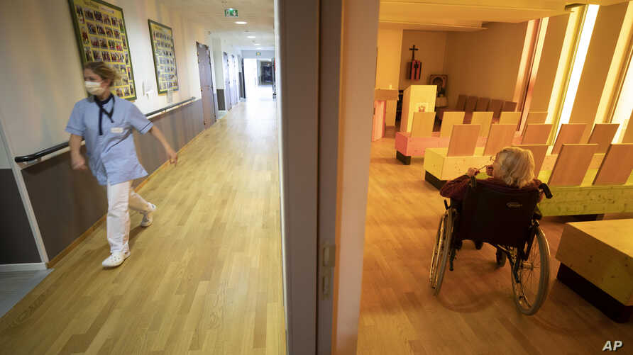 FILE - A nurse walks in a corridor of a nursing home as a resident sits in a chapel