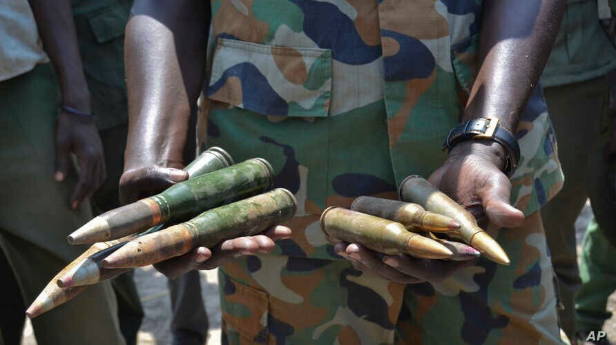 In this photo taken Saturday, Aug. 19, 2017, South Sudanese army commander Col. James Gatjiath holds ammunition captured from…